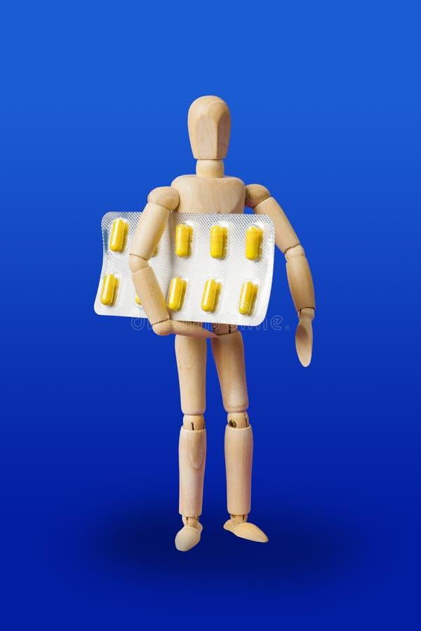 与药片的木玩具形象在蓝色 库存图片
