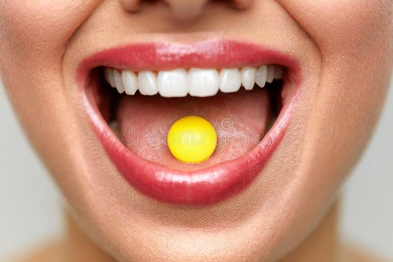 与药片的美丽的妇女嘴在舌头 女孩医学采取 库存照片