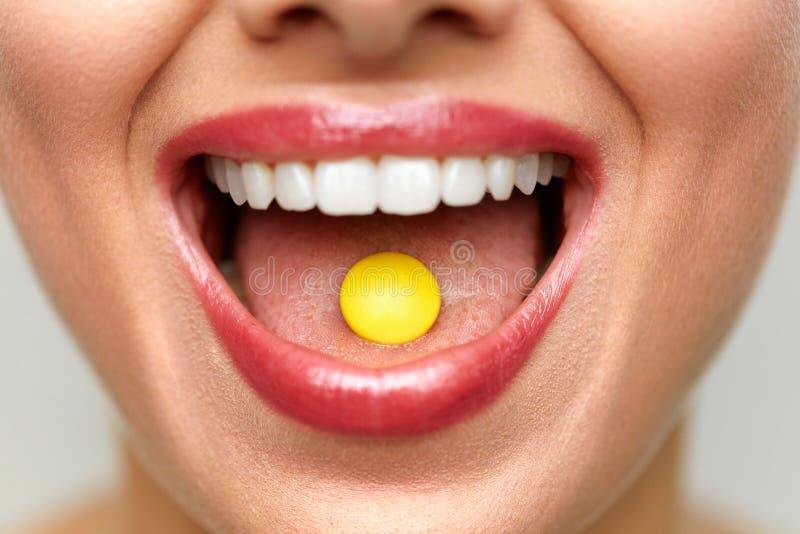 与药片的美丽的妇女嘴在舌头 女孩医学采取 免版税库存照片