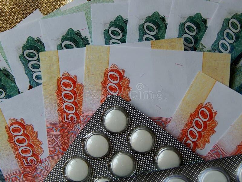 与药片的金钱在金黄背景 药物治疗的费用的概念 免版税图库摄影