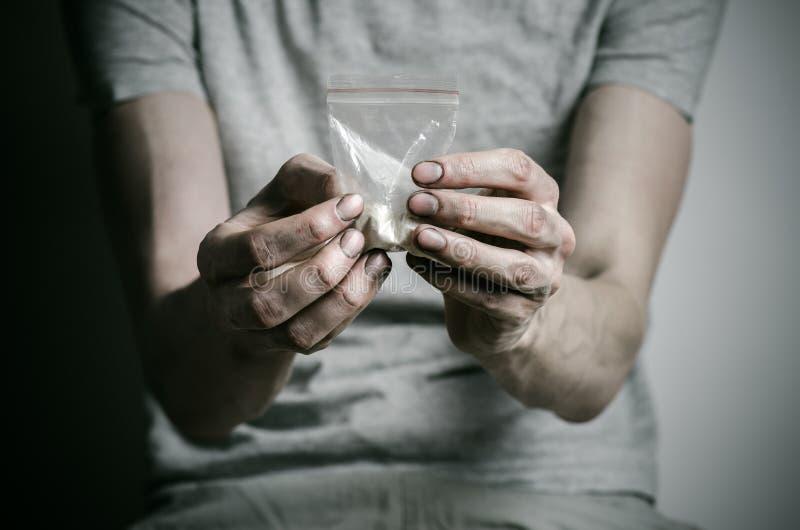 与药物和毒瘾题目的战斗:使拿着可卡因包裹上瘾在一件灰色T恤杉的在的黑暗的背景 图库摄影