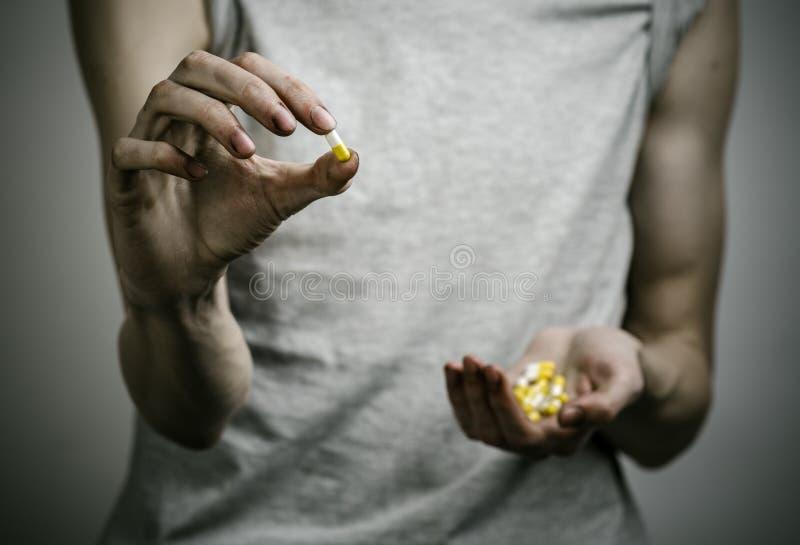 与药物和毒瘾题目的战斗:使拿着在黑暗的背景的麻醉药片上瘾 免版税图库摄影