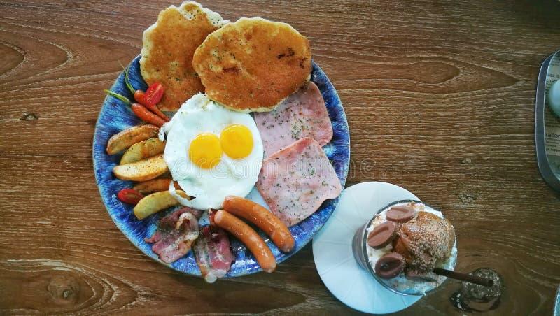 与荷包蛋、火腿、香肠、烟肉、嫩胡萝卜、被烘烤的土豆和被冰的巧克力的生气勃勃早餐在木桌上 库存图片