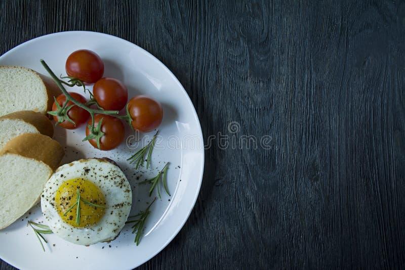 与荷包蛋的牛排在香料 装饰用迷迭香、新鲜的樱桃和面包片 归档在一块白色板材 ?? 图库摄影