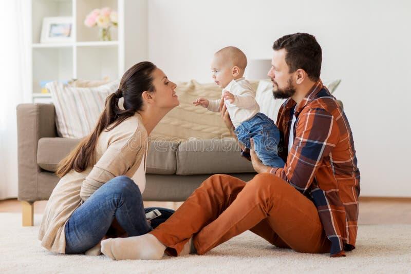 与获得的婴孩的愉快的家庭乐趣在家 免版税图库摄影