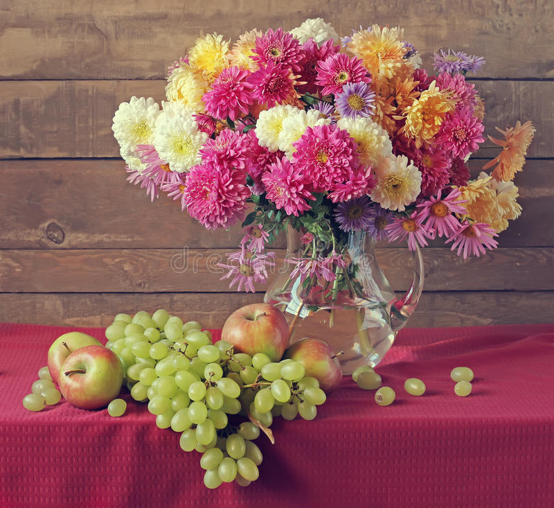 与菊花在一个透明水罐,葡萄的静物画和 免版税库存照片