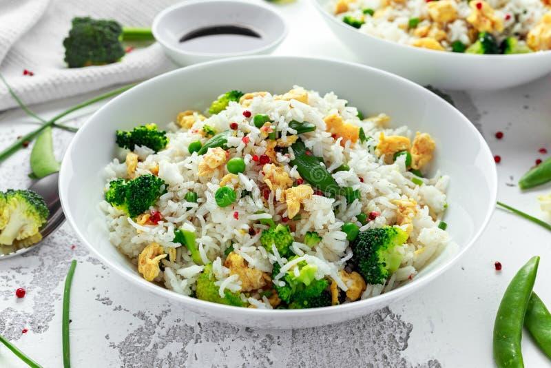与菜、硬花甘蓝、豌豆和鸡蛋的炒饭在一个白色碗 酱油 健康的食物 免版税库存照片