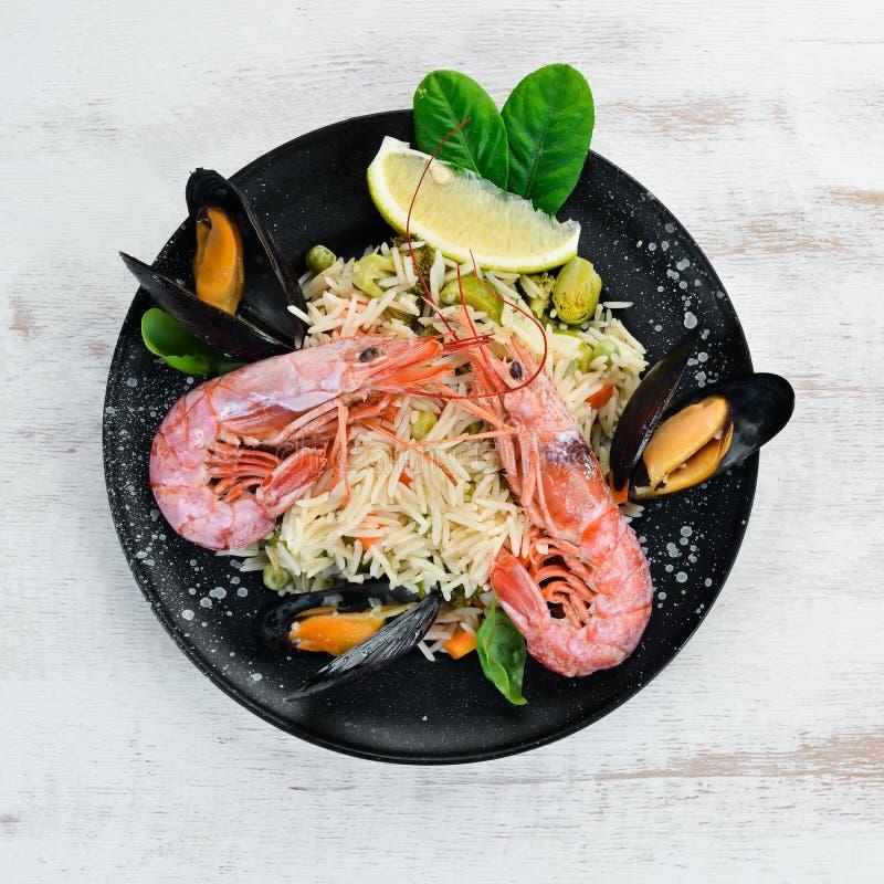 与菜和海鲜的意大利煨饭米 虾和淡菜 在老背景 免版税库存照片