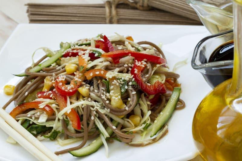 与菜和芝麻特写镜头的日本soba沙拉在桌上的一块板材 面条沙拉 荞麦面条与 库存图片