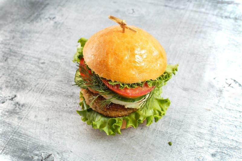 与菜和草本的大beaf牛排汉堡在土气木背景 库存照片