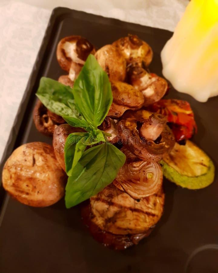 与菜和草本的烤招标蘑菇在板材 免版税库存图片