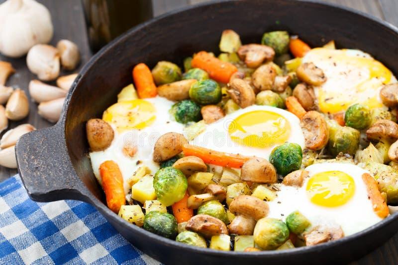 与菜和蘑菇的被烘烤的鸡蛋 库存图片