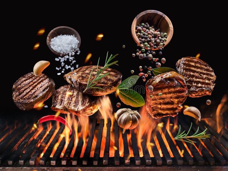与菜和香料的烤牛排飞行在发光的格栅烤肉火 免版税库存图片