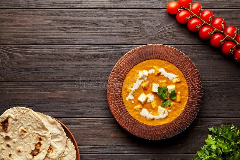 与菜和黄油paneer乳酪的沙赫paneer传统印度素食食物在黑暗的木背景 库存图片