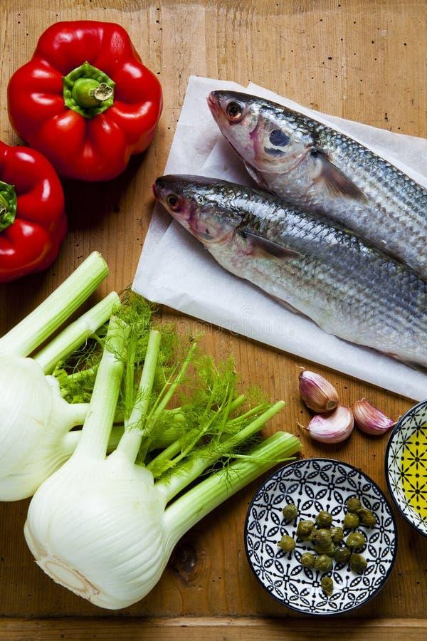 与菜成份的未加工的鲜鱼在木纹理ta 库存照片