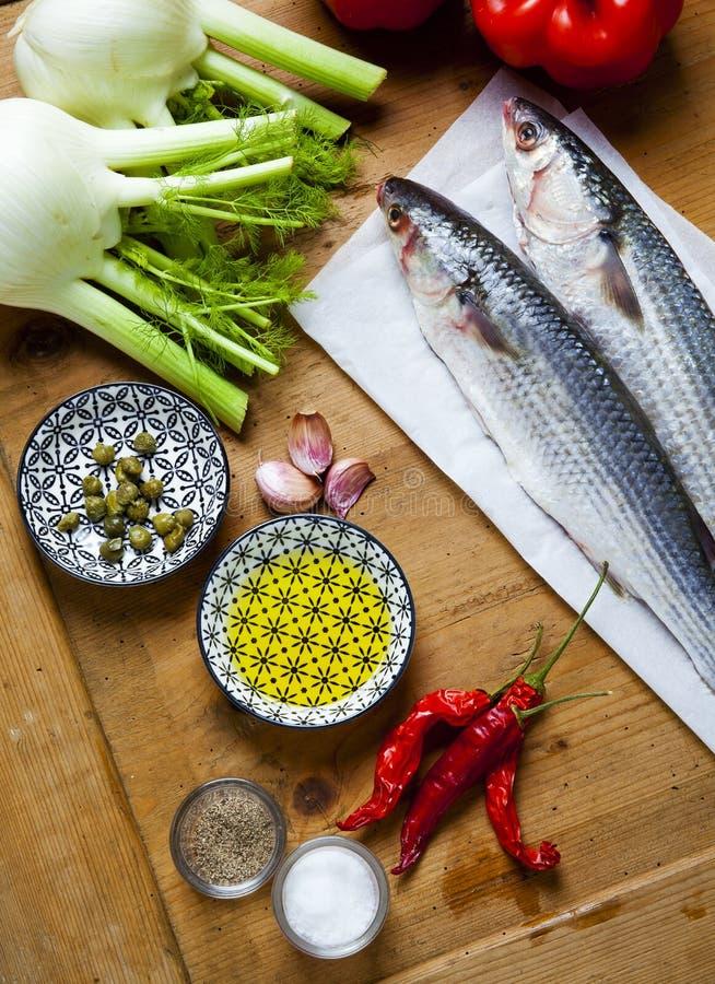 与菜成份的未加工的鲜鱼在木纹理ta 免版税库存图片