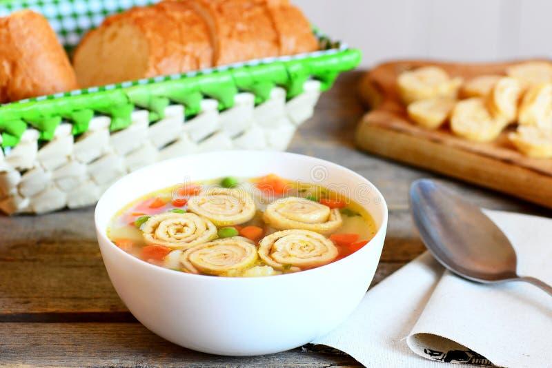 与菜混合的可口汤和在碗的油煎的煎蛋卷 在切片,在土气木背景的匙子上添面包 图库摄影
