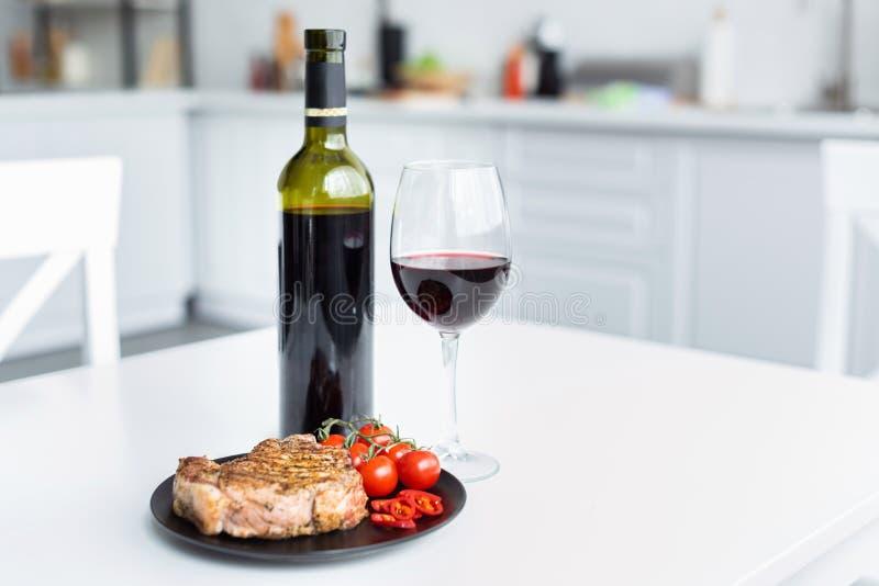 与菜的可口烤牛排在板材和红酒 库存图片