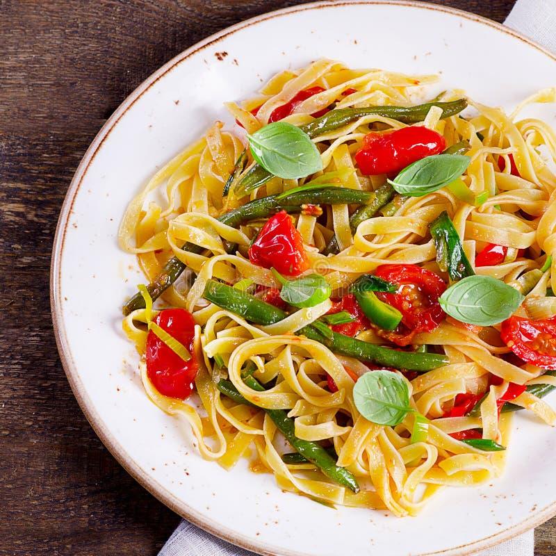 与菜的意大利面团在一个木板 免版税库存照片