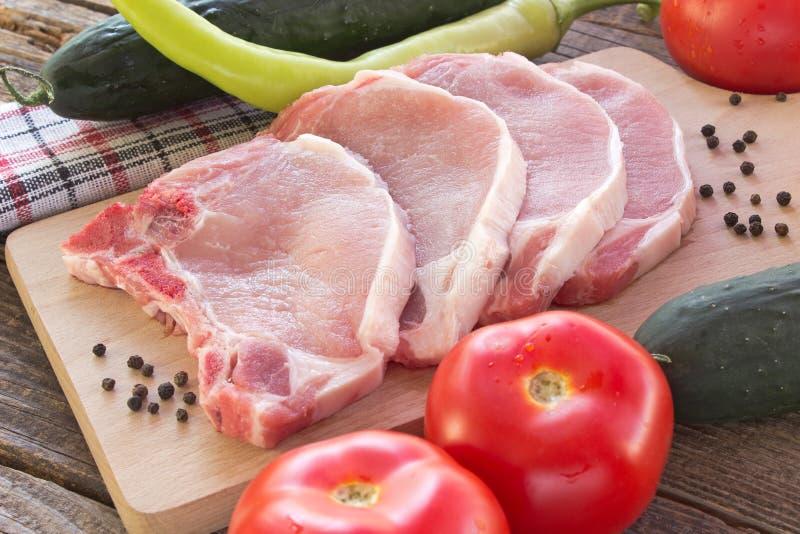 与菜的未加工的猪排肉在桌上 库存图片
