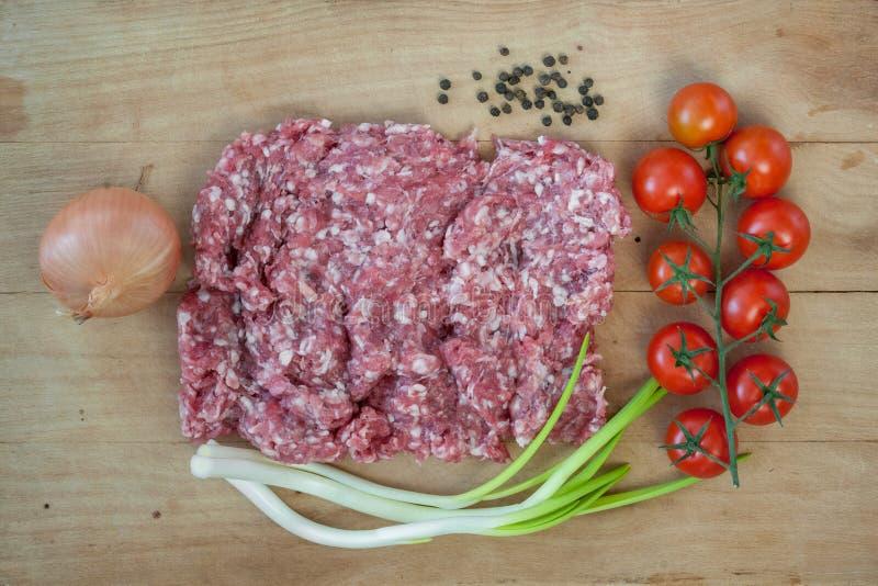 与菜的未加工的肉末在一张木桌上 免版税图库摄影