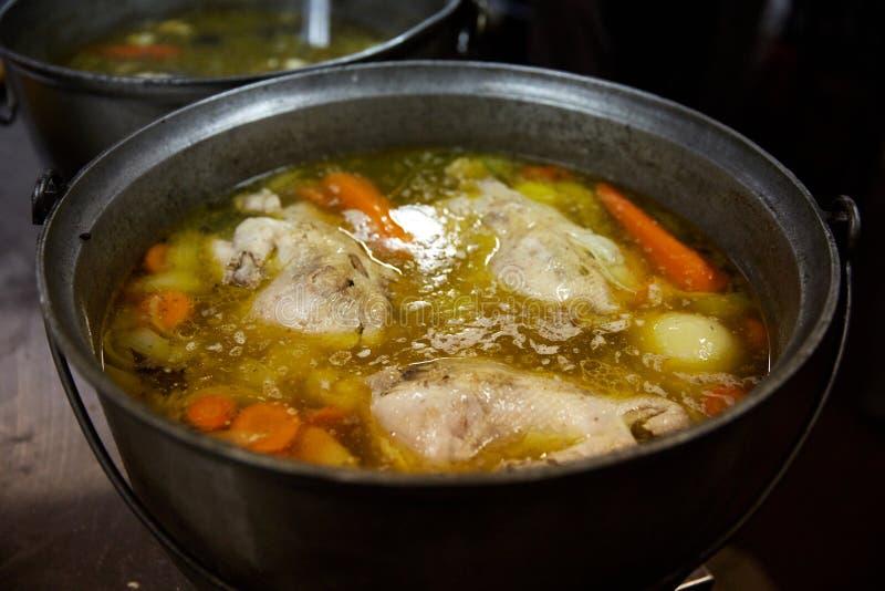 与菜的汤在火炉被烹调在厨房里 免版税库存图片