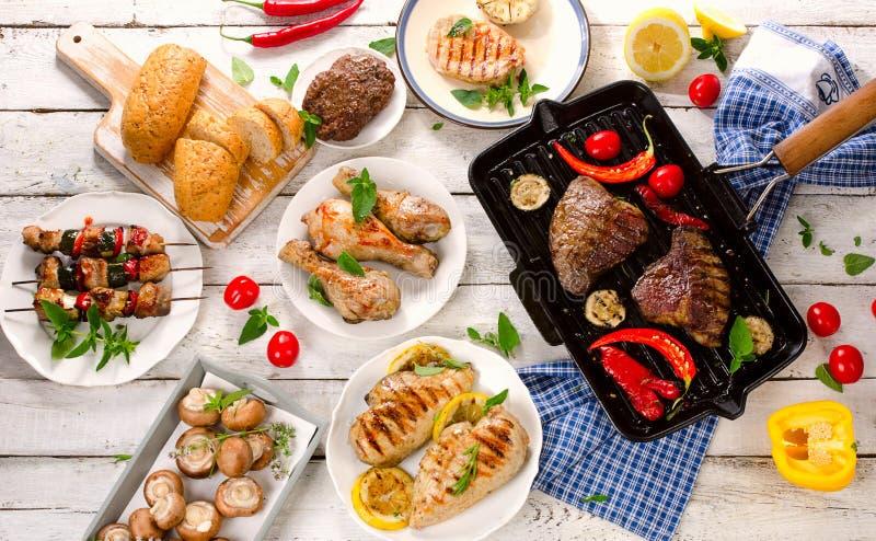 与菜的混杂的烤肉在一张白色木桌上 图库摄影