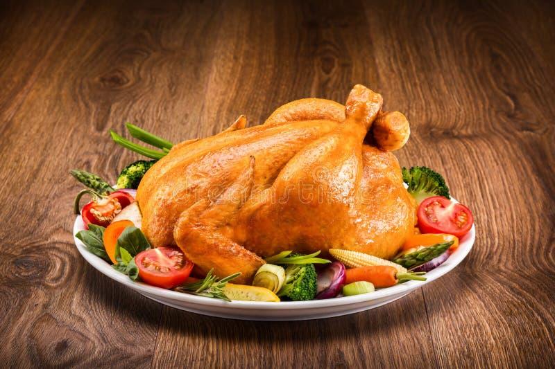 与菜的烤鸡在一张木桌上 库存图片