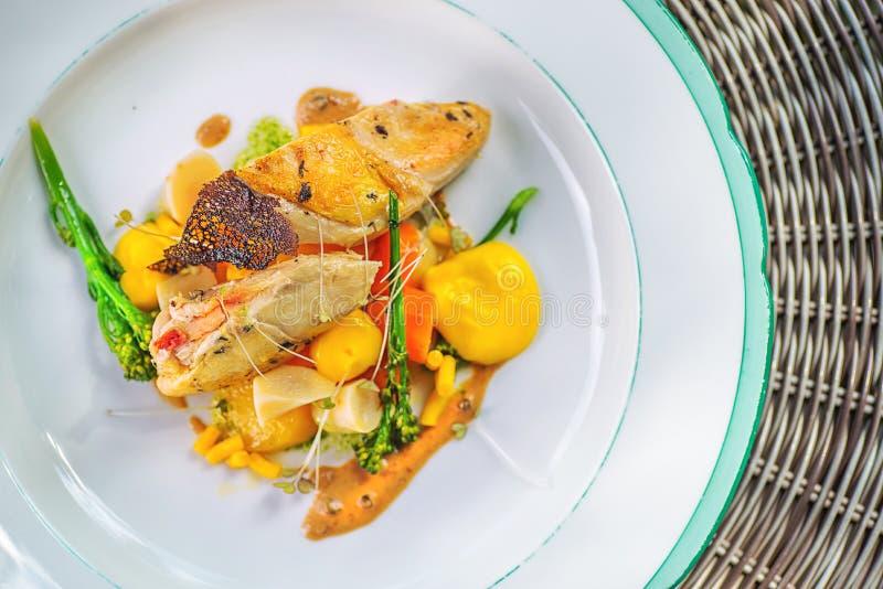 与菜的烤鸡大腿在白色板材,专属餐馆的产品摄影 图库摄影