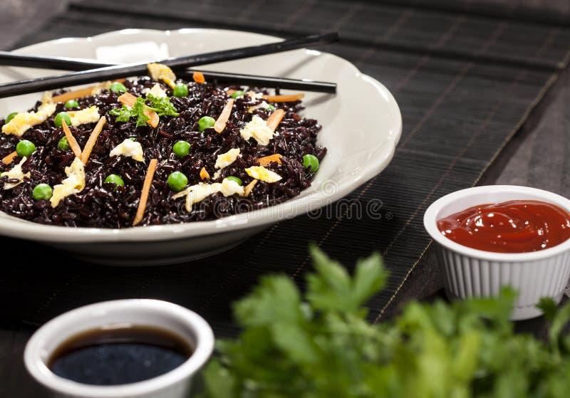 与菜的煮熟的黑米在一块板材用调味汁和筷子在木背景 库存图片