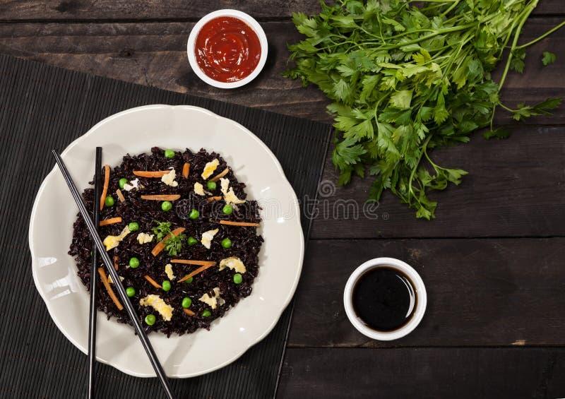 与菜的煮熟的黑米在一块板材用调味汁和筷子在木背景 免版税库存图片