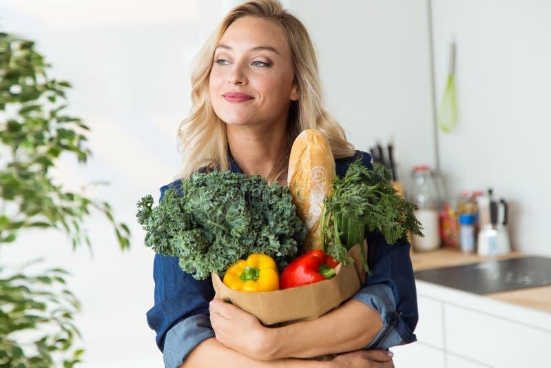 与菜的美丽的少妇买菜袋子在家 免版税库存照片