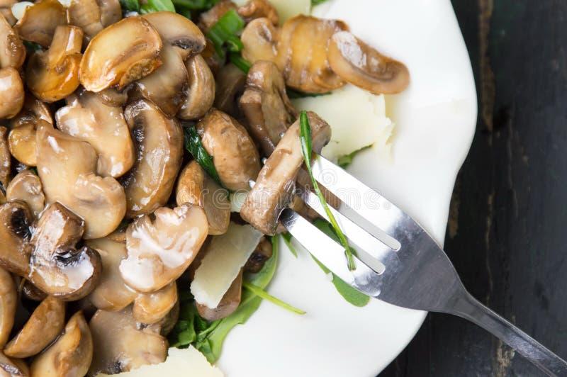 与菜的蘑菇在一块白色板材 免版税库存图片