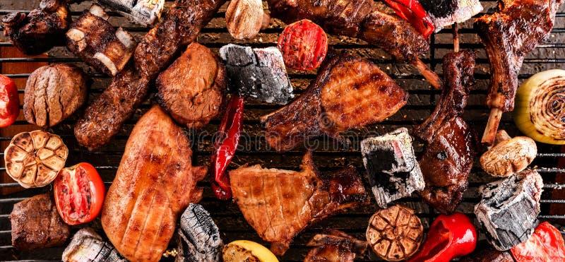 与菜的被分类的可口烤肉在烤肉的煤炭,与火光的黑暗的背景  r 免版税库存图片