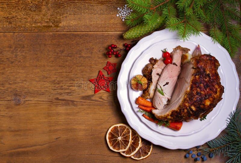与菜的被烘烤的火腿:红萝卜、葱、蕃茄、大蒜和草本 圣诞节装饰生态学木 的圣诞前夕盘 免版税图库摄影