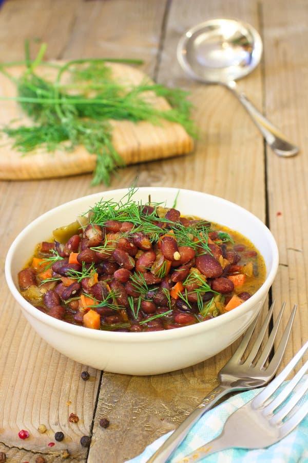 与菜的被烘烤的豆在木土气桌上 免版税库存照片