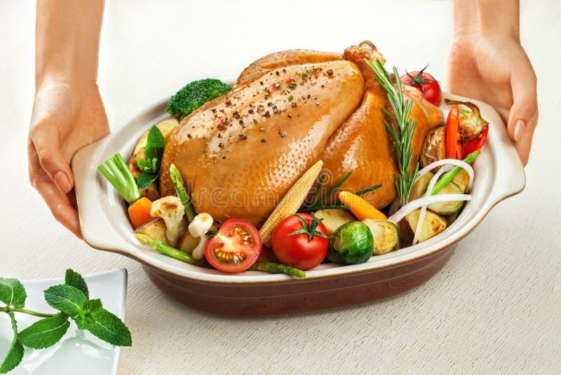 与菜的被烘烤的鸡在白色背景在手中隔绝的盘 库存图片