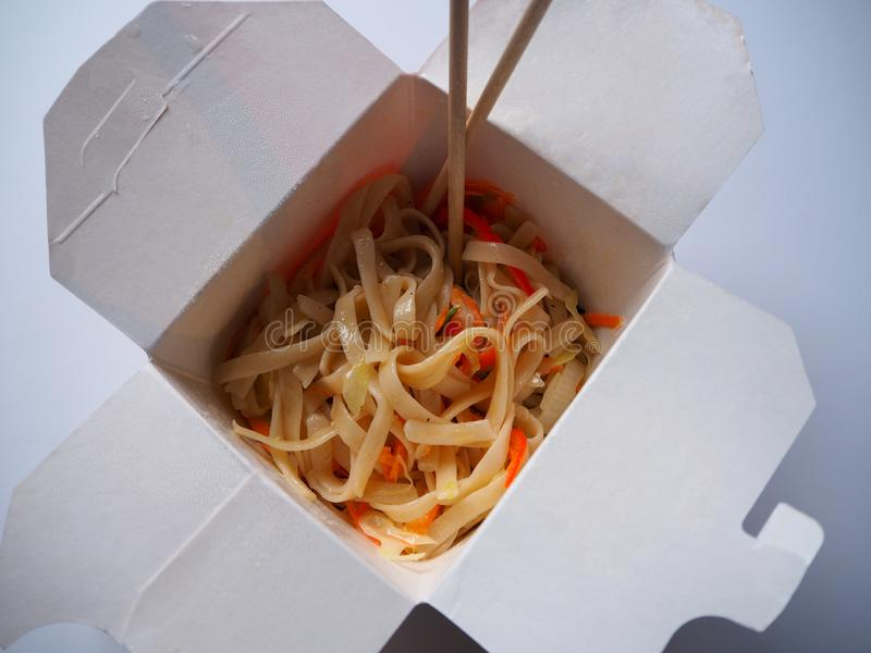 与菜的面条在白色背景的外卖箱子 免版税库存照片