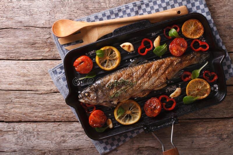 与菜的鳟鱼在桌上的一个格栅平底锅 水平 图库摄影
