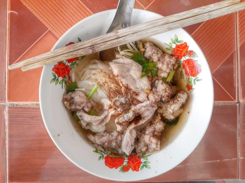 与菜,猪肉骨头汤,可口泰国食物的切好的猪肉面条,在桌上把几勺筷子放 免版税库存照片