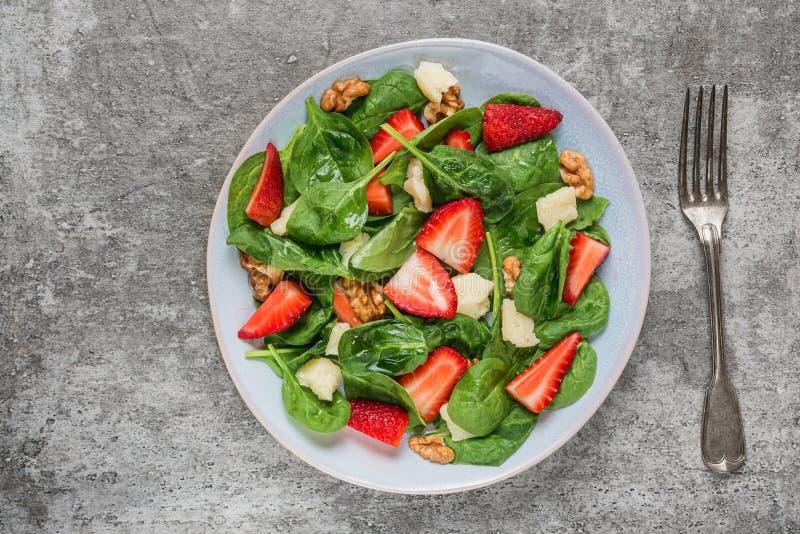 与菠菜叶子、帕尔马干酪和核桃的新鲜的草莓沙拉与叉子 健康keto饮食食物 免版税库存照片