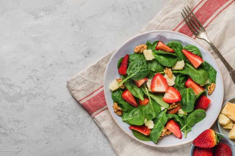 与菠菜叶子、草莓、帕尔马干酪、橄榄油和核桃的夏天沙拉 健康keto饮食食物 库存图片