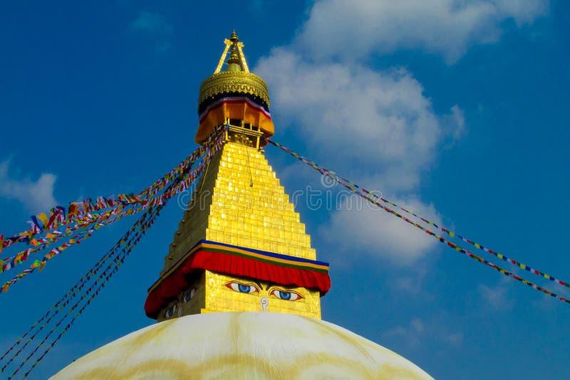 与菩萨眼睛和西藏祷告旗子的Stupa在尼泊尔 免版税库存图片