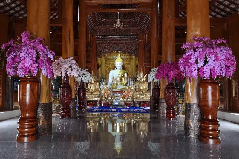 与菩萨雕象和兰花的美好的佛教木寺庙内部在Wat Bandensali开花在泰国 库存图片