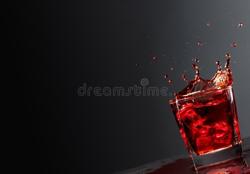与落的冰块的可乐玻璃在黑暗的背景 库存照片