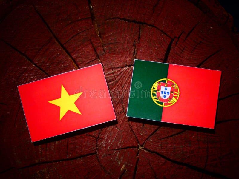 与葡萄牙旗子的越南旗子在被隔绝的树桩 库存图片
