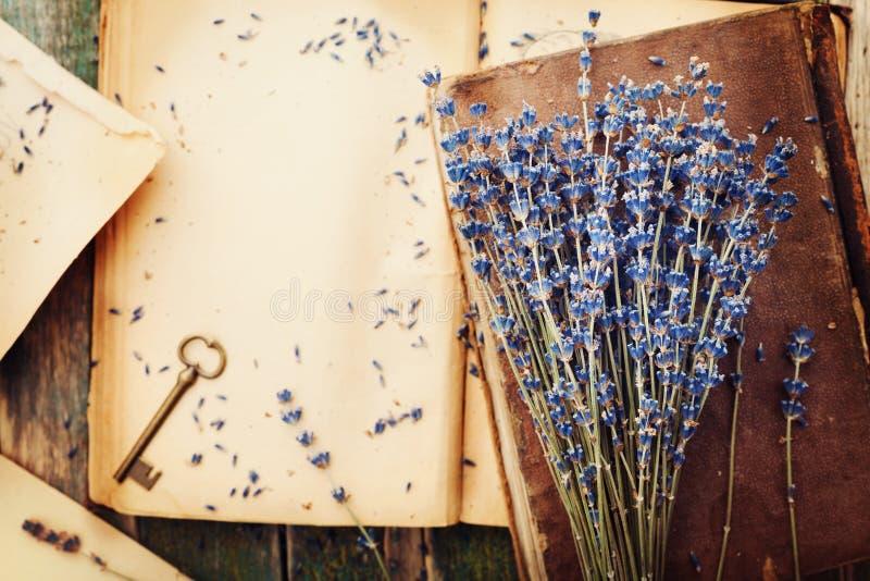 与葡萄酒书、钥匙和淡紫色的减速火箭的静物画开花,在木台式视图的怀乡构成 库存照片