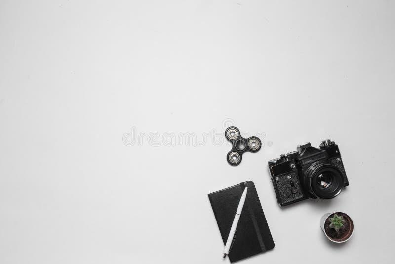 与葡萄酒减速火箭的照相机的最小的与笔的构成,日志和在白色书桌上的坐立不安锭床工人 平的位置,顶视图 库存图片