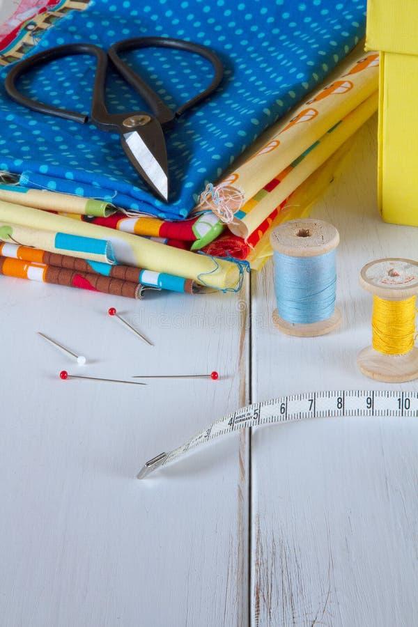 与葡萄酒剪刀、别针、测量的磁带和棉花螺纹的五颜六色的织品在白色木桌上 库存图片