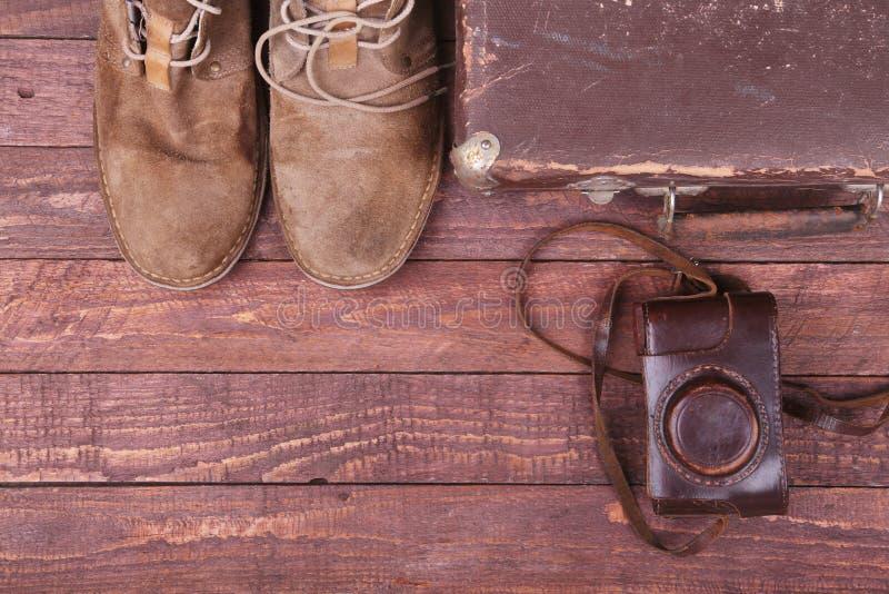 与葡萄酒手提箱、太阳镜、老照相机、绒面革起动、盒金钱的和护照的旅行概念在木地板上 库存照片